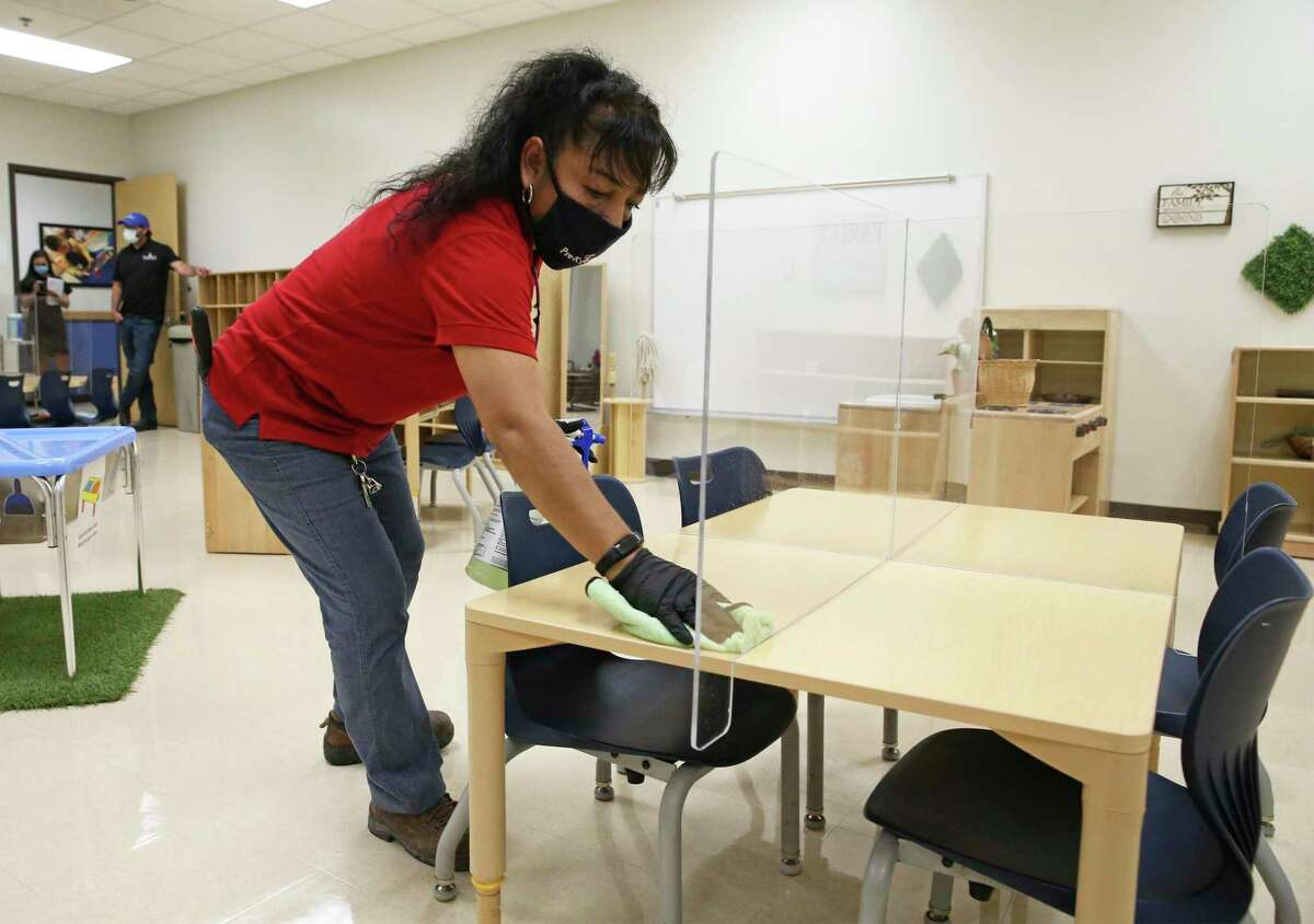 Evelia Garcia cleans desk spaces as Pre-K 4 SA CEO Sarah Baray shows measures taken by the Pre-K 4 SA North Center to combat spread of COVID-19 on Aug. 19, 2020.