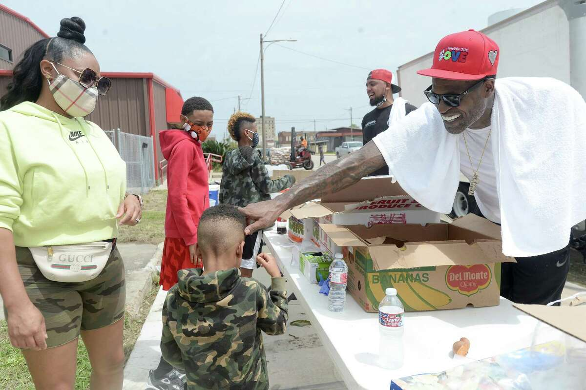 Port Arthur native and NBA player Stephen Jackson greets a young volunteer as he with Feed Your City Challenge's food and supply distribution to those impacted by Hurricane Laura in Port Arthur. Photo taken Saturday, September 5, 2020 Kim Brent/The Enterprise