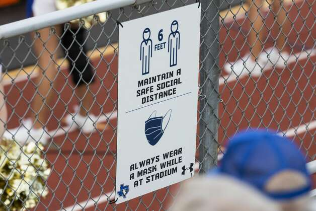 A sign reminding football fans to maintain safe social distancing and to wear a mask is placed on the fence at Blue Jay Stadium on Friday, Sept. 4, 2020 in Needville. The UIL has sent out warnings to schools to keep stadiums within 50 percent capacity, for spectators to wear masks and other coronavirus precautions. Photo: Brett Coomer/Staff Photographer / © 2020 Houston Chronicle