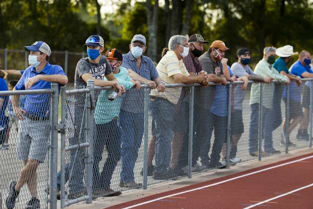 Needville football fans stand along the fence next to the football field watch a game against Hargrave at Blue Jay Stadium on Friday, Sept. 4, 2020 in Needville. The UIL has sent out warnings to schools to keep stadiums within 50 percent capacity, for spectators to wear masks and other coronavirus precautions. Photo: Brett Coomer/Staff Photographer / © 2020 Houston Chronicle