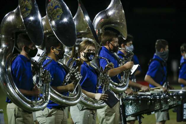 The Needville band wear masks just before taking the field for the halftime show during a high school football game against Hargrave at Blue Jay Stadium on Friday, Sept. 4, 2020 in Needville. The UIL has sent out warnings to schools to keep stadiums within 50 percent capacity, for spectators to wear masks and other coronavirus precautions. Photo: Brett Coomer/Staff Photographer / © 2020 Houston Chronicle