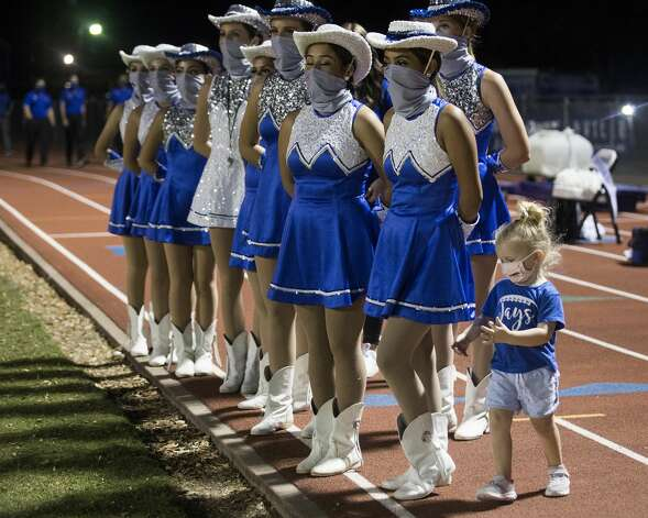 Sadie Jo Lawson wears a mask as she plays around the Needville High School Sapphires dance team during halftime of a football game at Blue Jay Stadium on Friday, Sept. 4, 2020 in Needville. The UIL has sent out warnings to schools to keep stadiums within 50 percent capacity, for spectators to wear masks and other coronavirus precautions. Photo: Brett Coomer/Staff Photographer / © 2020 Houston Chronicle