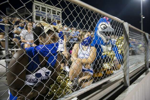 Needville cheerleaders Morgan Scott, left, and Riley Anderson watch the band perform at halftime of a high school football game against Hargrave at Blue Jay Stadium on Friday, Sept. 4, 2020 in Needville. The UIL has sent out warnings to schools to keep stadiums within 50 percent capacity, for spectators to wear masks and other coronavirus precautions. Photo: Brett Coomer/Staff Photographer / © 2020 Houston Chronicle