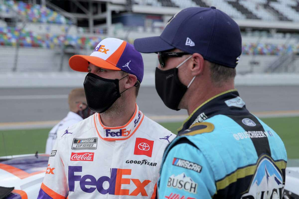 DAYTONA BEACH, FLORIDA - AUGUST 16: Denny Hamlin, driver of the #11 FedEx Freight Toyota, and Kevin Harvick, driver of the #4 Busch Beer National Forest Foundation Ford, talk on the grid prior to the NASCAR Cup Series Go Bowling 235 at Daytona International Speedway on August 16, 2020 in Daytona Beach, Florida. (Photo by Chris Graythen/Getty Images)