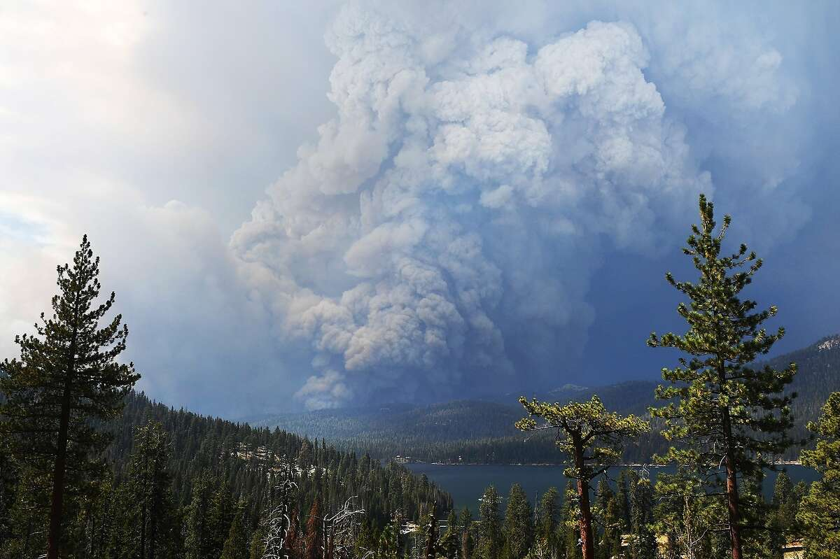 Plumes of smoke rise into the sky as a wildfire burns on the hills near Shaver Lake, Calif., Saturday, Sept. 5, 2020. Fires in the Sierra National Forest have prompted evacuation orders as authorities urged people seeking relief from the Labor Day weekend heat wave to stay away from the popular lake. (Eric Paul Zamora/The Fresno Bee via AP)