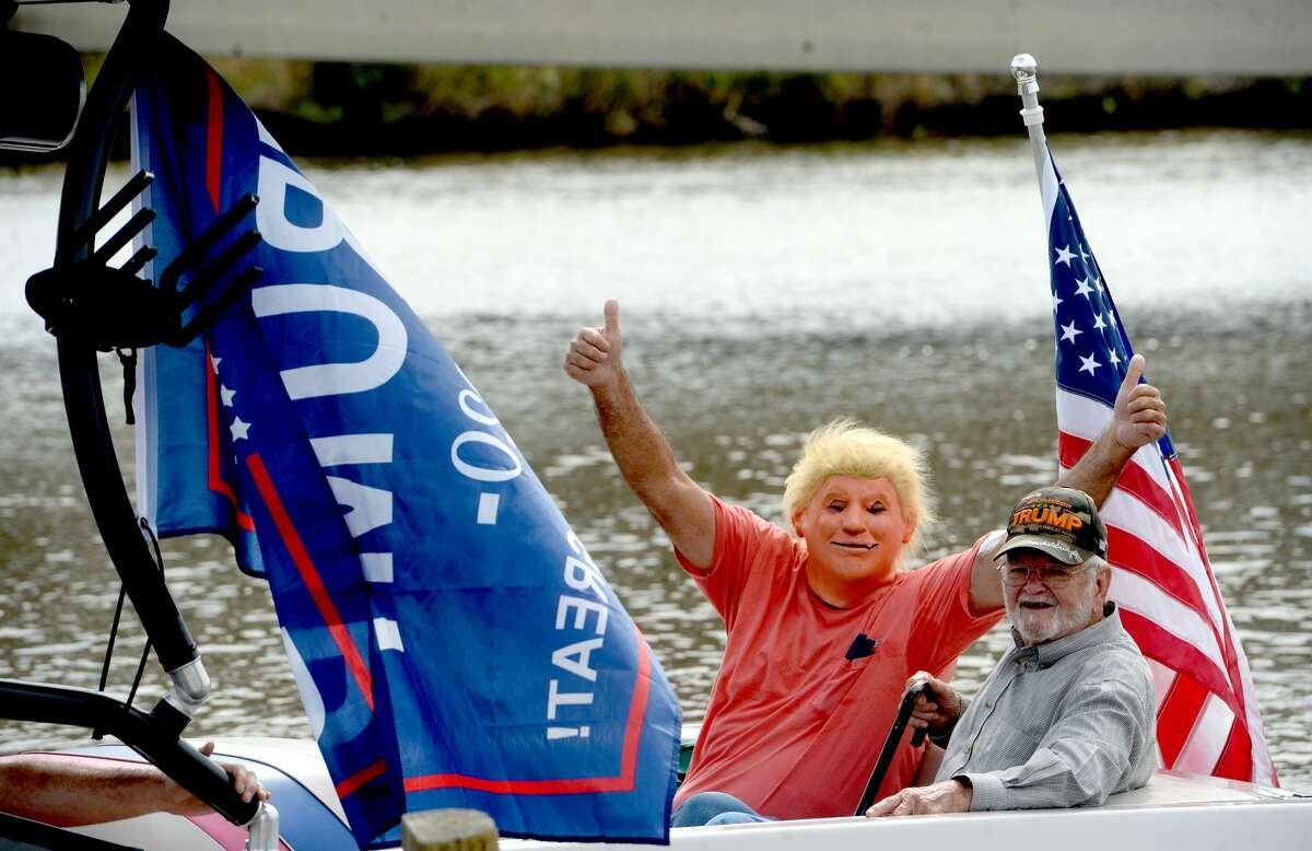 Boaters push out from Ancelet's Marina beneath the Rainbow Bridge during Saturday's Trump Boat Parade 2020 up the Neches River. Crowds packed the riverfront in Port Neches to cheer on the hundreds of boats as they passed, chanting