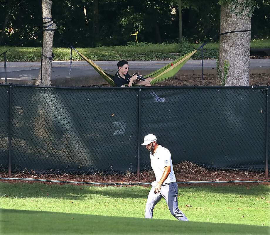 A golf fan gets creative hanging a hammock between trees for a view over the fence while Dustin Johnson goes about his round. Photo: Curtis Compton / Atlanta Journal-Constitution
