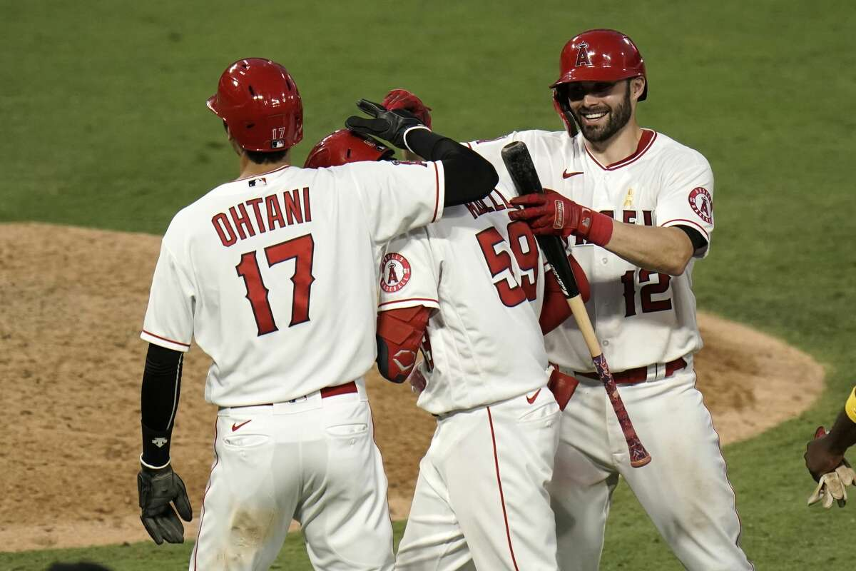 Los Angeles Angels' Jo Adell, center, is congratulated by Shohei Ohtani, right, of Japan, and Anthony Bemboom after hitting a walkoff single in the seventh inning of the first baseball game of a doubleheader against the Houston Astros, Saturday, Sept. 5, 2020, in Anaheim, Calif. (AP Photo/Jae C. Hong)