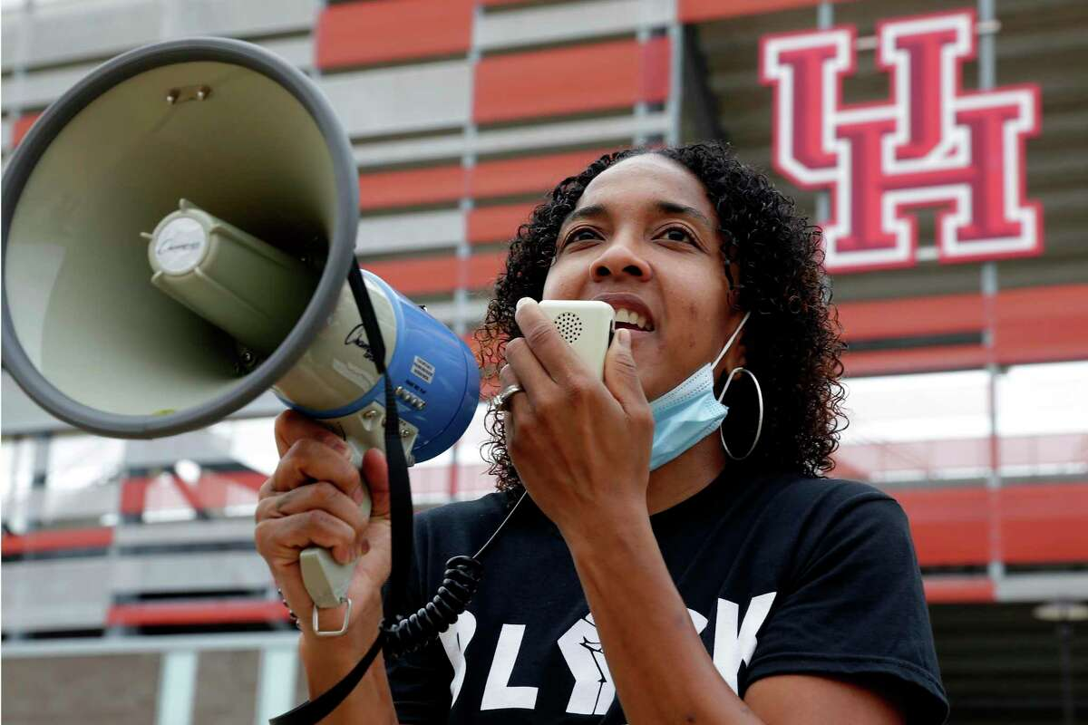 Tai Dillard, University of Houston women's basketball assistant coach, uses a bull horn to update student athletes, coaches and staff as they all gather outside of TDECu Stadium before taking part take part in a racial injustice protest and march across the UH campus Saturday, Sep. 5, 2020 in Houston, TX.