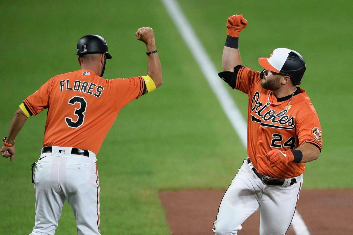 Baltimore Orioles' DJ Stewart (24) celebrates his home run with third base coach Jose Flores (3) during the sixth inning of the team's baseball game against the New York Yankees, Saturday, Sept. 5, 2020, in Baltimore. (AP Photo/Nick Wass)