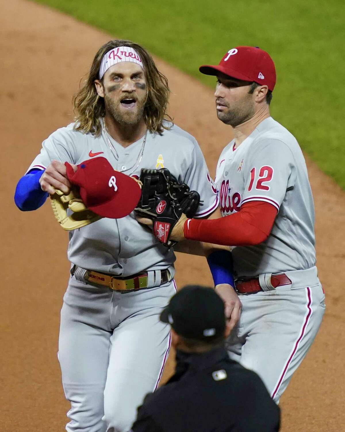 Philadelphia Phillies' Bryce Harper, left, reacts next to Neil Walker (12) after umpire Roberto Ortiz, below, threw him out of the team's baseball game against the New York Mets during the fifth inning Saturday, Sept. 5, 2020, in New York. (AP Photo/John Minchillo)
