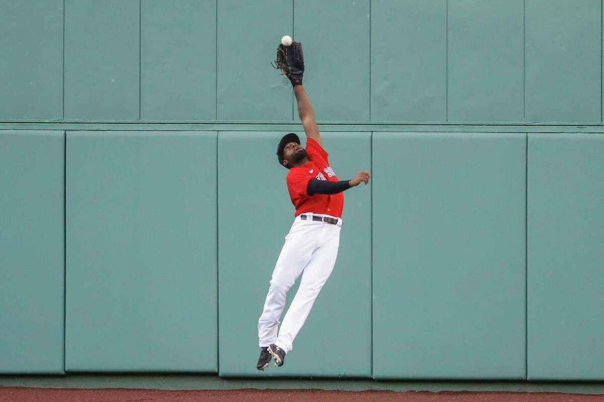 Boston Red Sox center fielder Jackie Bradley Jr. makes a leaping catch on a ball hit by Toronto Blue Jays' Rowdy Tellez during the sixth inning of the first baseball game of a doubleheader Friday, Sept. 4, 2020, at Fenway Park in Boston. (AP Photo/Winslow Townson)