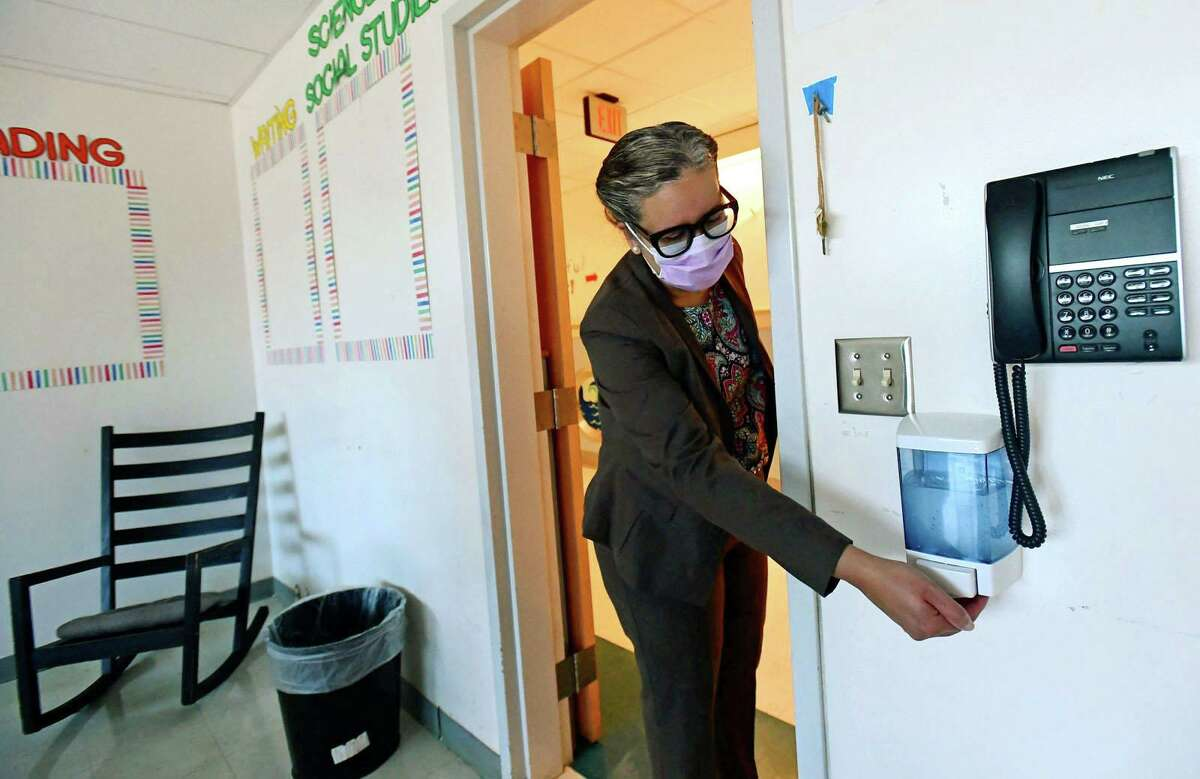 New superintendent Dr. Alexandra Estrella uses sanitizer dispenser that is inn each classroom as new principal Christina Guerra leads a walk through of Brookside Elementary School Friday, September 4, 2020, to show the last minute safety preparartions taking place at the school in Norwalk, Conn.