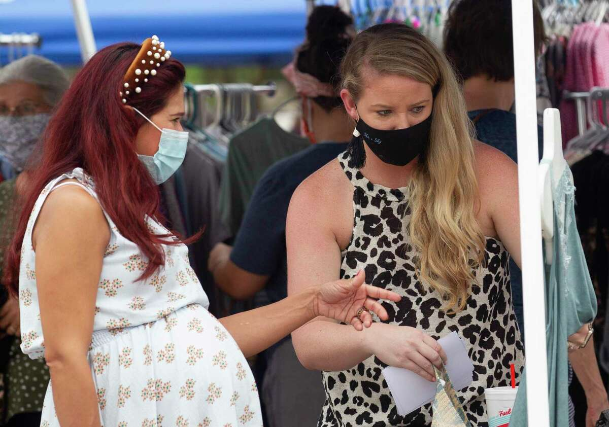 Katelyn Thomason, with Audacious Grace Boutique, helps Elisa Ward look for clothing at the new Oak Ridge Pop Up Market on Saturday in Oak Ridge.