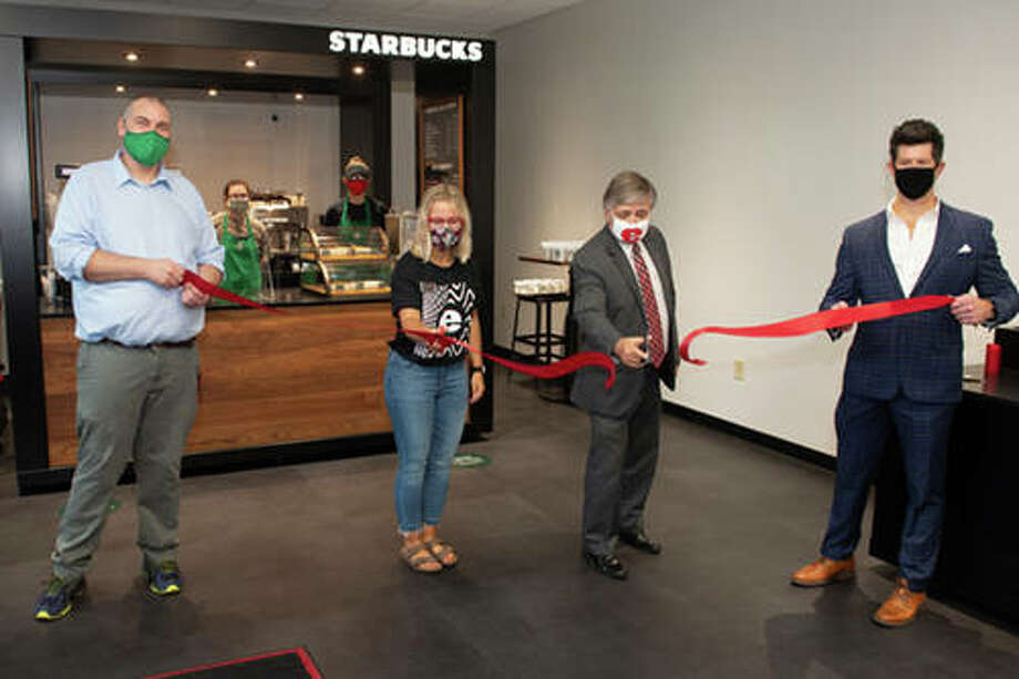 Southern Illinois University Edwardsville Dining Services Administrator Matt Turner, left, and Director Dennis Wobbe, right, hold the ceremonial ribbon while SIUE Student Government President Maddie Walters, second left, and Chancellor Randy Pembrook, second right, cut it, marking the official opening of the Starbucks Library Cart. Photo: For The Telegraph