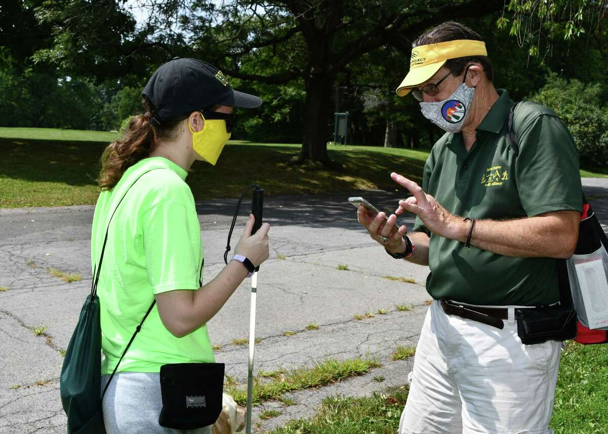 Megan Hale and Capital Region Nordic Alliance Executive Director Russ Myer prepare to use software on an iPhone in Albany's Washington Park on Aug. 25, 2020. Hale, a student/athlete at Hudson Valley Community College, is testing out a program that eventually will be used by blind paralympic athletes in the sport of trail orienteering. (Joyce Bassett / Special to the Times Union)
