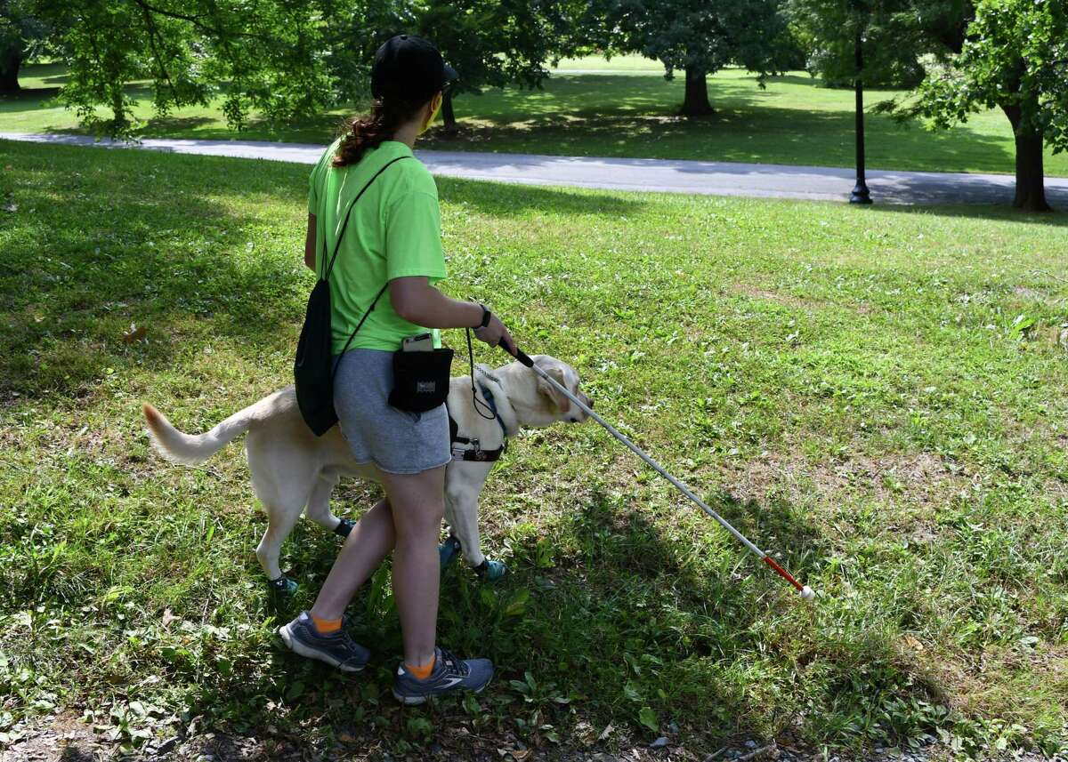 Megan Hale and her guide dog Hero test out a program that eventually will be used by blind paralympic athletes in the sport of trail orienteering. Hale, a student/athlete at Hudson Valley Community College, participated in the testing in Albany's Washington Park on Aug. 25, 2020. (Joyce Bassett / Special to the Times Union)