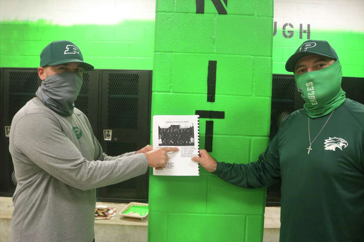 Robert Espinoza (left) and David Zapien point to their names in a 1998 baseball program when the two were 13-year-olds. Now they're finally together again as Pasadena High School varsity football coaches.