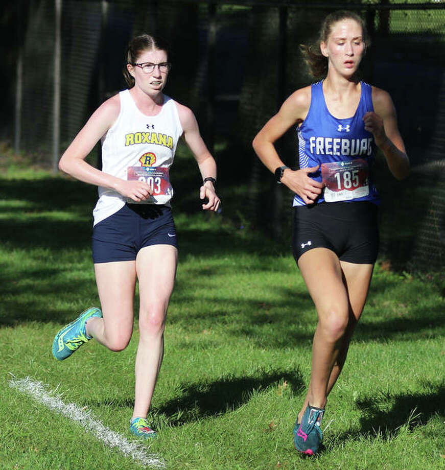 Roxana's Riley Doyle (left) and Freeburg's Abby Holcomb run on the lead in the third mile in the Class 1A girls heat Saturday morning at the Granite City Invite at Wilson Park. Holcomb won the heat, with Doyle placing second. Photo: Greg Shashack / The Telegraph