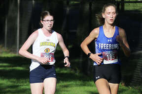 Roxana's Riley Doyle (left) and Freeburg's Abby Holcomb run on the lead in the third mile in the Class 1A girls heat Saturday morning at the Granite City Invite at Wilson Park. Holcomb won the heat, with Doyle placing second.