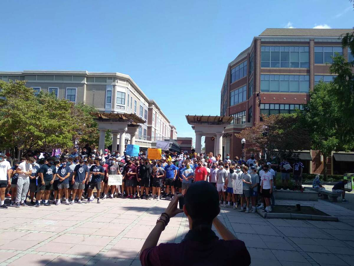 Football players reassemble at Blue Back Square in West Hartford on Sunday after marching to and from Town Hall and holding a rally demanding a Connecticut high school football season. Players at Sunday's rally represented a range of schools around the state. In Fairfield County, a group of players assembled for a brief video for social media, asking for