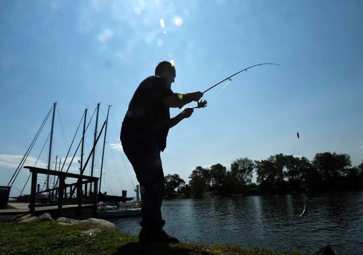 Darien's Robert Konstantinis catches a fish while fishing with his son, Evan, 11, at Shippan Landing in Stamford, Conn. Sunday, Sept. 6, 2020. Stamford saw beautiful weather all weekend with high temperatures in the low-80s.