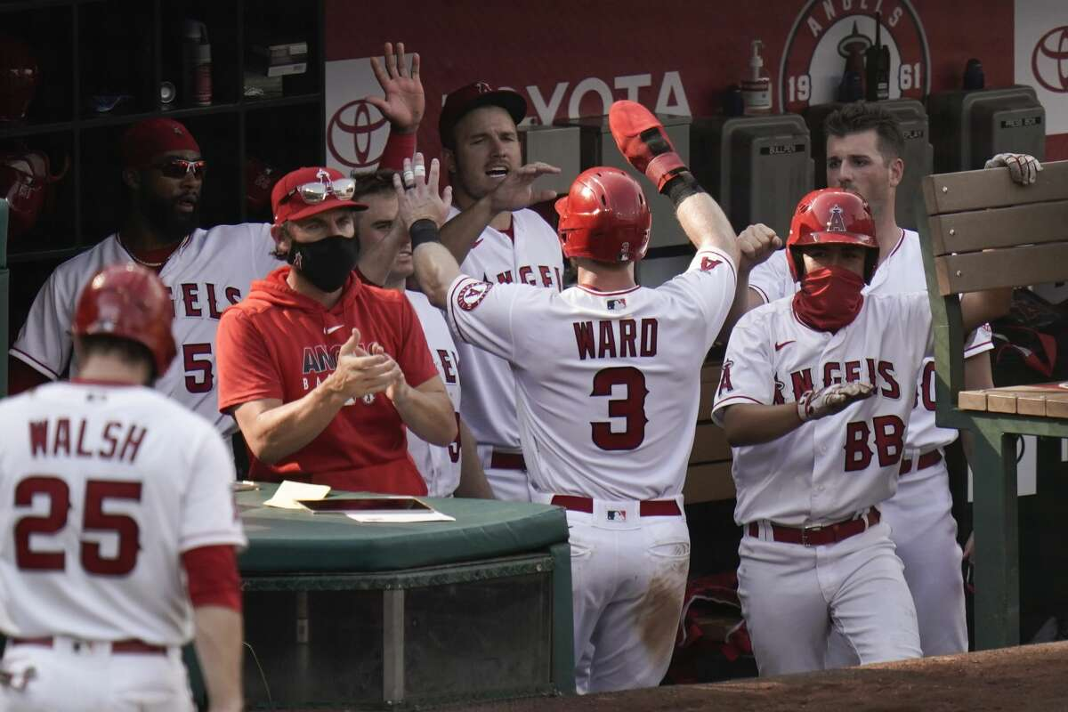 Los Angeles Angels' Taylor Ward, center, is greeted by teammates after he scored on a single hit by Justin Upton during the eighth inning of a baseball game against the Houston Astros, Sunday, Sept. 6, 2020, in Anaheim, Calif. (AP Photo/Jae C. Hong)
