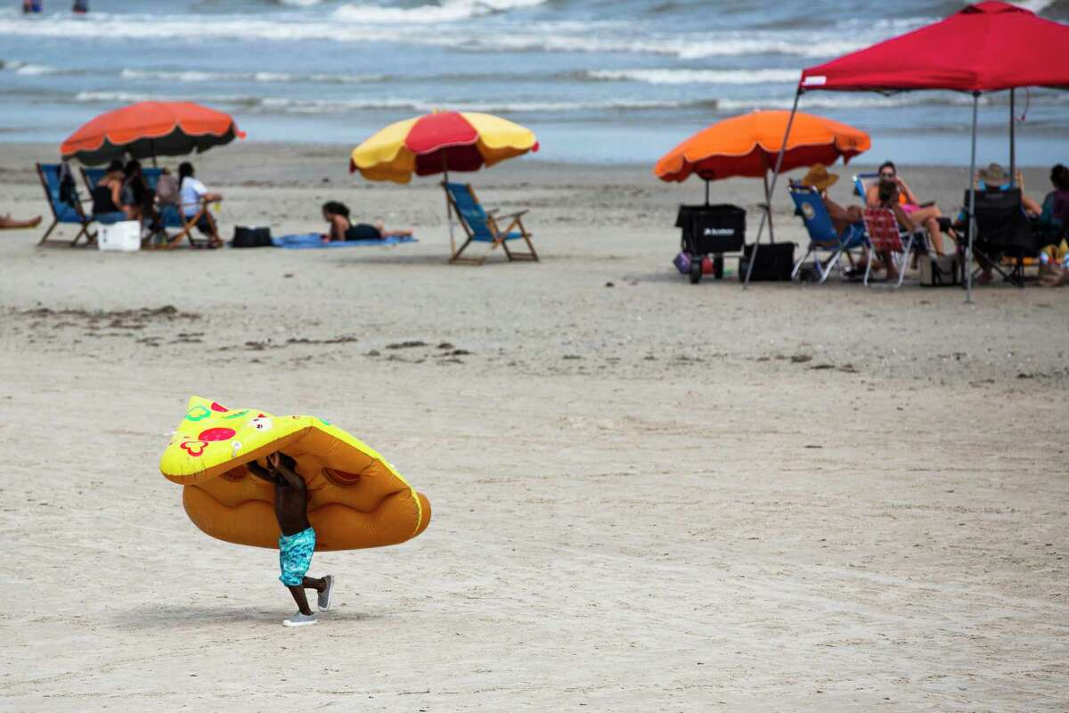 Zachary Hart, 5, drags a floater in the shape of a slice of pizza on Labor Day weekend on Saturday, Sept. 5, 2020, in Galveston. Hart and his family came to enjoy the beach in Galveston from Dallas.