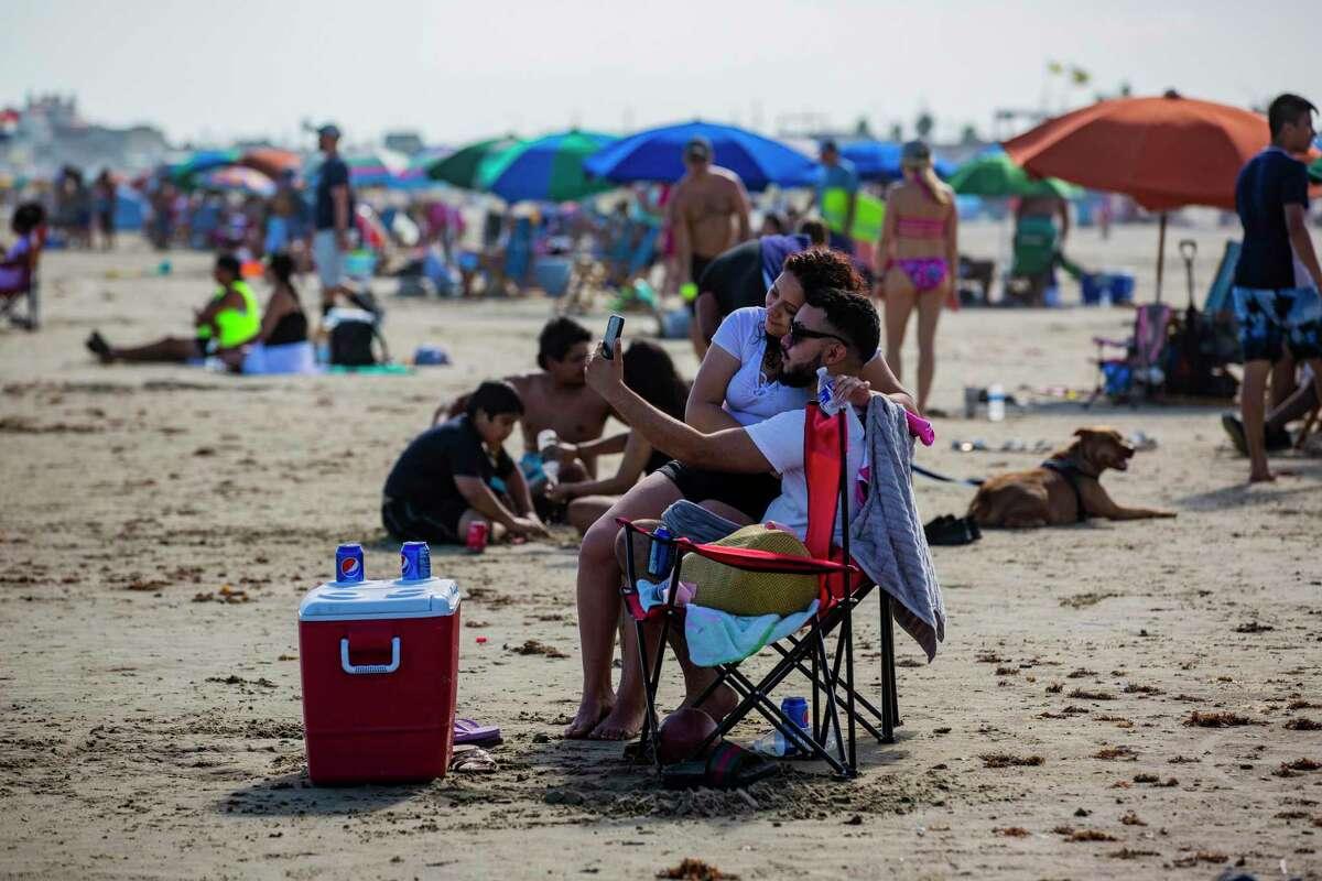 Yenifer Sanchez and Franklin Carvajal pose for a selfie together at Stewart Beach on Saturday in Galveston.