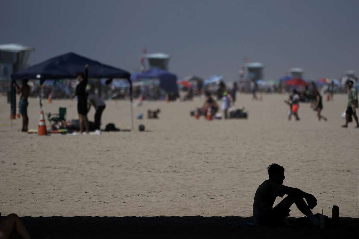 A man sits in the shade underneath a pier in Huntington Beach, Calif., Saturday, Sept. 5, 2020. California is sweltering under a dangerous heat wave Labor Day weekend that was spreading triple-digit temperatures over much of the state, raising concerns about power outages and the spread of the coronavirus as throngs of people packed beaches and mountains for relief. (AP Photo/Jae C. Hong)