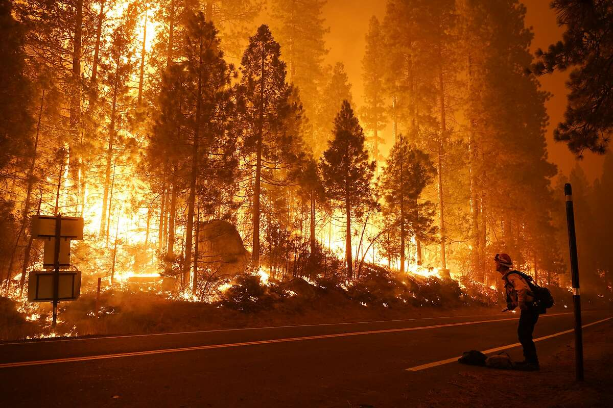 Gabe Huck, right, a member of a San Benito Monterey Cal Fire crew, stands along state Highway 168 while fighting the Creek Fire, Sunday, Sept. 6, 2020, in Shaver Lake, Calif. (AP Photo/Marcio Jose Sanchez)
