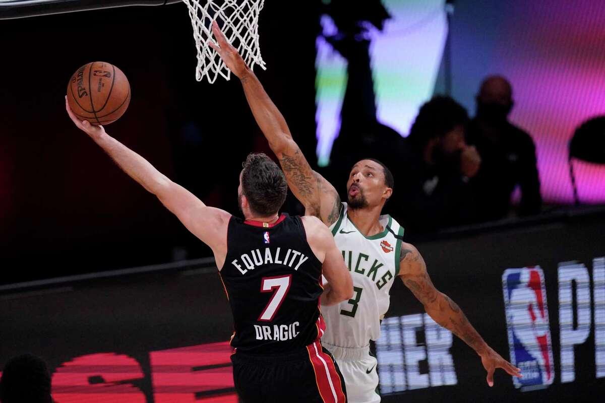 Miami Heat's Goran Dragic shoots past Milwaukee Bucks' Wesley Matthews during the second half of an NBA conference semifinal playoff basketball game Sunday, Sept. 6, 2020, in Lake Buena Vista, Fla. (AP Photo/Mark J. Terrill)