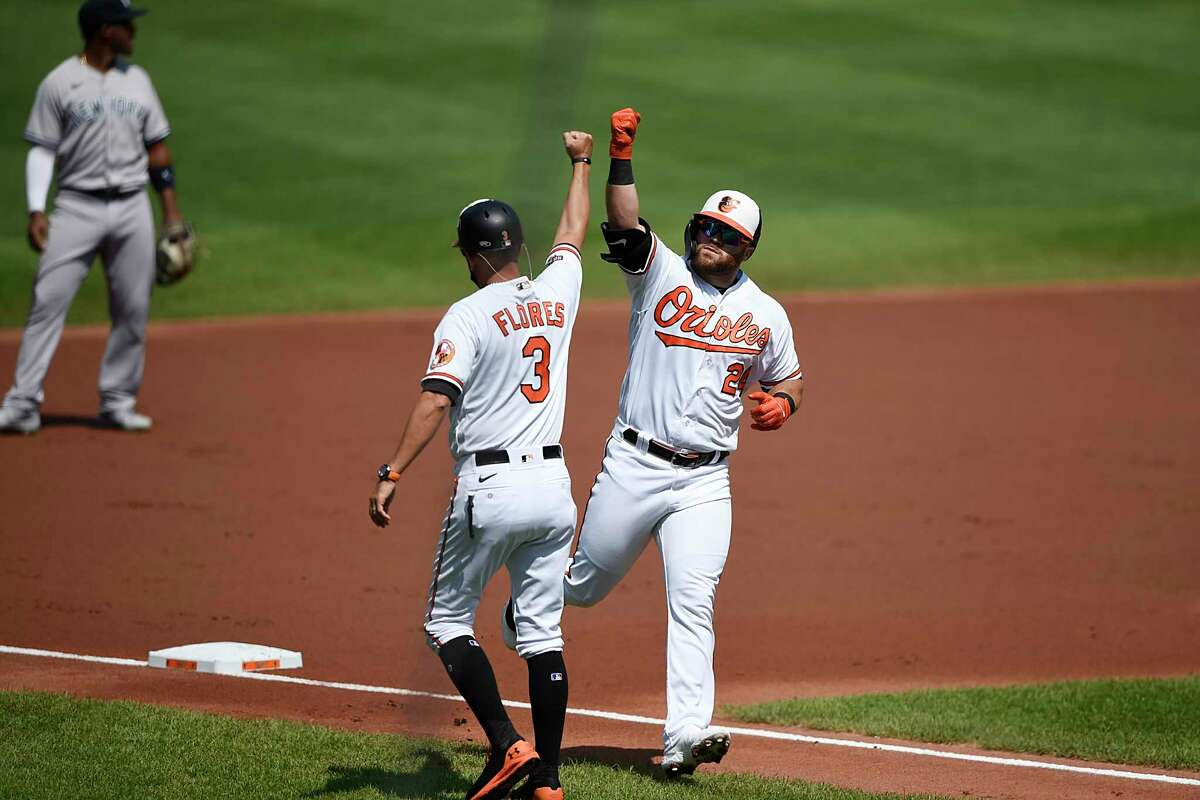 Baltimore Orioles' DJ Stewart, right, is congratulated by third base coach Jose Flores after hitting a two-run home run against the New York Yankees in the first inning of a a baseball game, Sunday, Sept. 6, 2020, in Baltimore, Md. (AP Photo/Gail Burton)