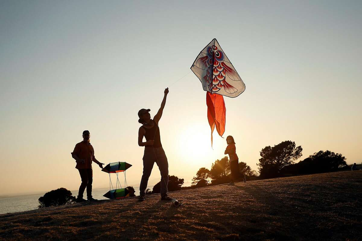 As the sun sets behind them, Elizabeth Peele and Michael Callahan fly a kite at Cesar Chavez Park in Berkeley, Calif., on Sunday, September 6, 2020.