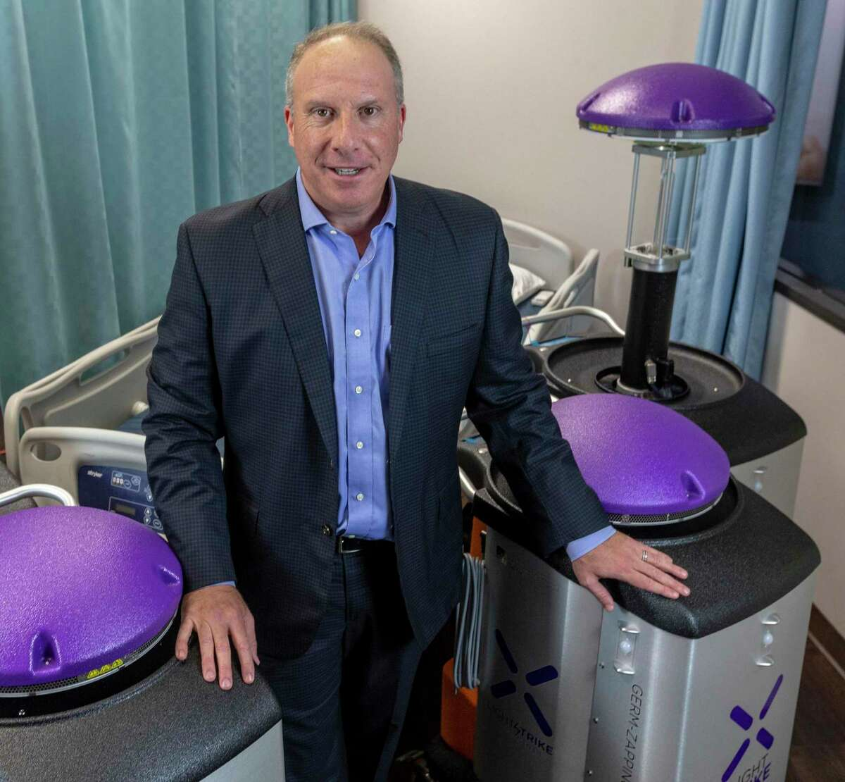 Morris Miller, CEO of Xenex, poses Wednesday, Sept. 2, 2020 with some of the company's LightStrike xenon-light-emitting disinfecting robots.