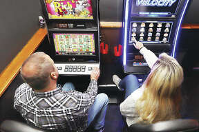 In this December photo, people try their luck on slot machines inside Bubby and Sissy's bar on Belle Street in Alton. City revenue from video gaming and the Argosy Casino Alton are down markedly this year because of the pandemic and state regulations related to the virus.