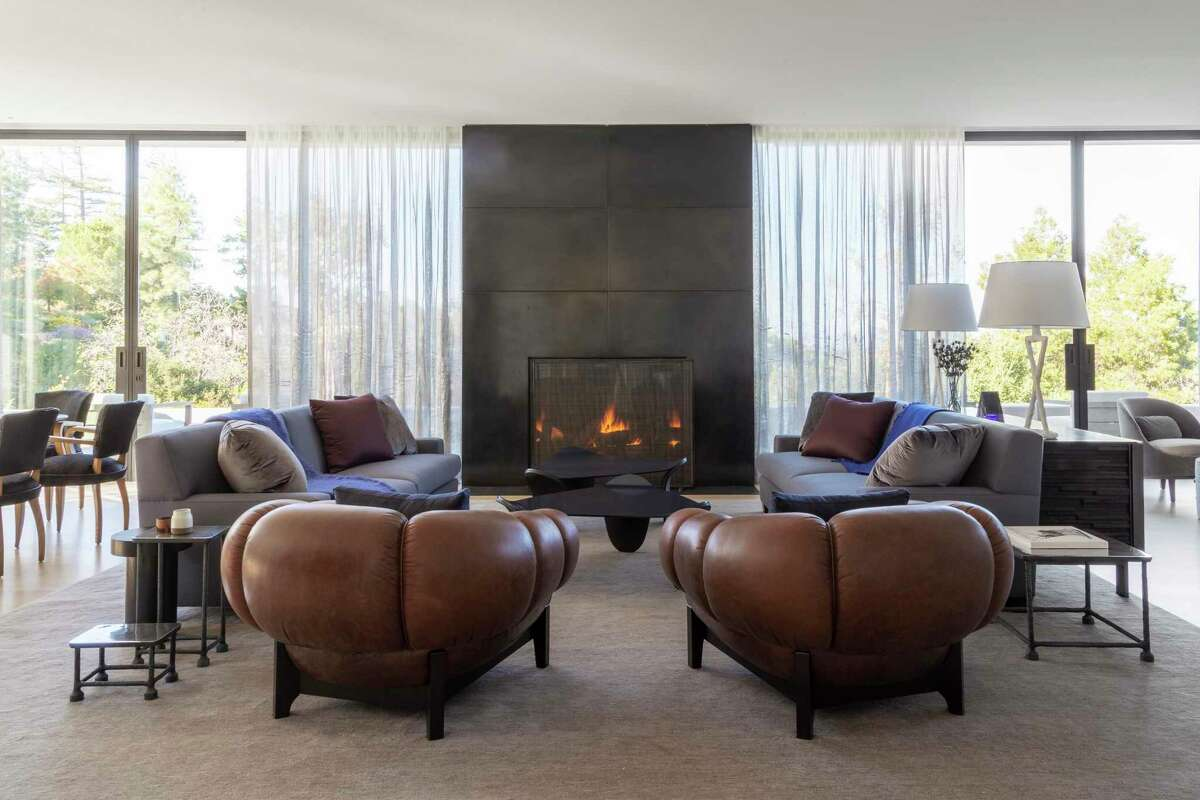 Floor-to-ceiling windows flank a gas fireplace in this great room conceptualized by Heather Hilliard Design.
