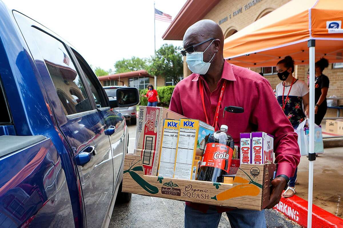 Judson ISD Attendance Officer Alanzo Jackson carries a box of food to a waiting truck as the JISD, Communities In Schools, and H-E-B partnered up with