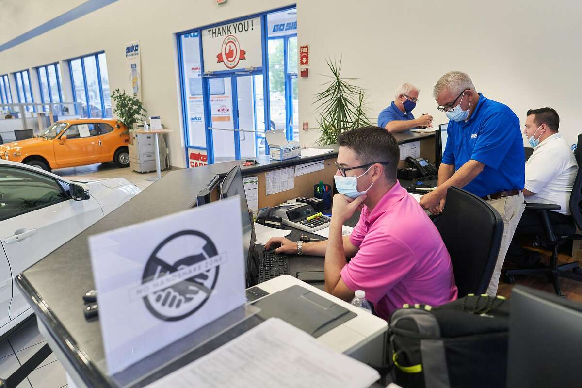 Salesmen at the Silko Honda dealership in Raynham, Mass., on Sept. 2, 2020. The president of Silko Honda says some low-mileage vehicles were snapped up within hours of arriving on the lot. (David Degner/The New York Times)