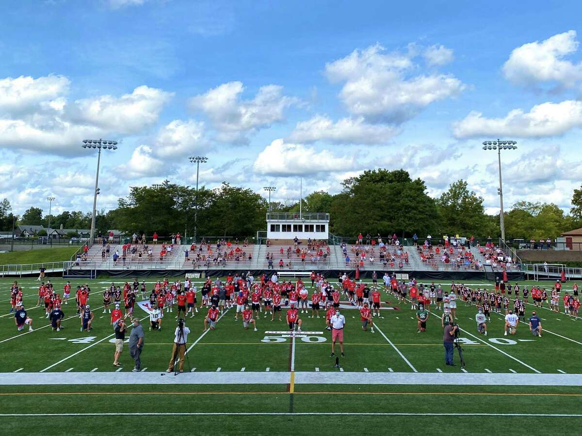 New Canaan football players are joined by town youth players in a show of support for tackle football at Dunning Stadium on Monday, Sept. 7, 2020. Parents of football players are in the bleachers. New Canaan's football captains were joined in the front row by captains of the Ludlowe, Norwalk and McMahon football teams.