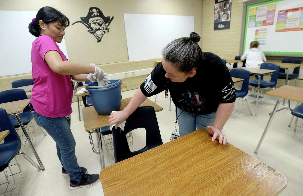 Tammy Hester, (right) head custodian for Vidor ISD, joins Marye Jane Cuntapay (left) and Tanya Crum in a classroom as they continue deep cleaning at Vidor High School Monday. Custodial staff, several of whom have volunteered their time off over spring break to complete cleaning projects at campuses throughout the district, will continue cleaning to get rid of any potential viruses and in preparation for school reconvening after the break is over next week. Photo taken Monday, March 16, 2020 Kim Brent/The Enterprise