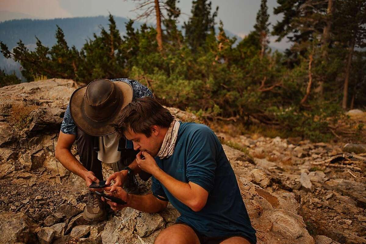 Stephen McKinley and Lucas Wojciechowski review maps and consider their options for avoiding the Creek Fire in the Sierra National Forest in California's Sierra Nevada on Saturday, Sept. 5.