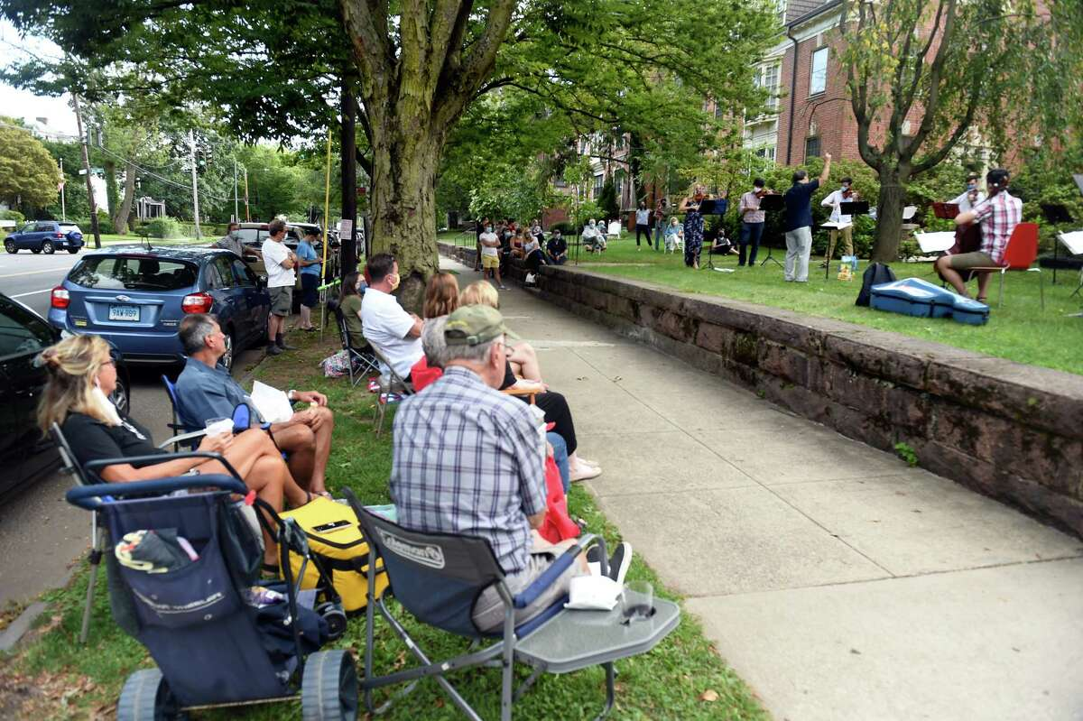 People set up seating next to the sidewalk to listen to Toshiyuki Shimada, Music Director of the Eastern Connecticut Symphony, the New Britain Symphony Orchestra and the Orchestra of the Southern Finger Lakes conduct the Music Amidst the Pandemic classical concert on the lawn of Whitney Walk in New Haven on September 7, 2020. The concert was organized by violinist Solomiya Ivakhiv, Head of Strings at the University of Connecticut.