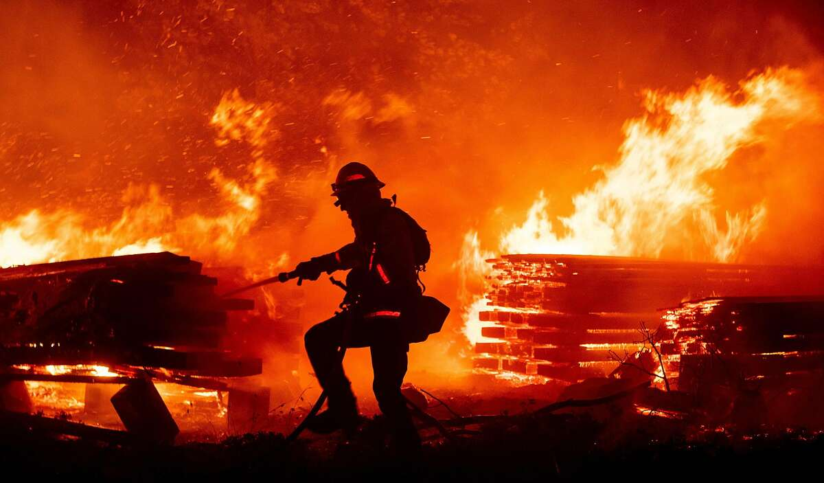A firefighter douses flames as they push towards homes during the Creek fire in the Cascadel Woods area of unincorporated Madera County, California on September 7, 2020. - A firework at a gender reveal party triggered a wildfire in southern California that has destroyed 7,000 acres (2,800 hectares) and forced many residents to flee their homes, the fire department said Sunday. More than 500 firefighters and four helicopters were battling the El Dorado blaze east of San Bernardino, which started Saturday morning, California Department of Forestry and Fire Protection (Cal Fire) said.