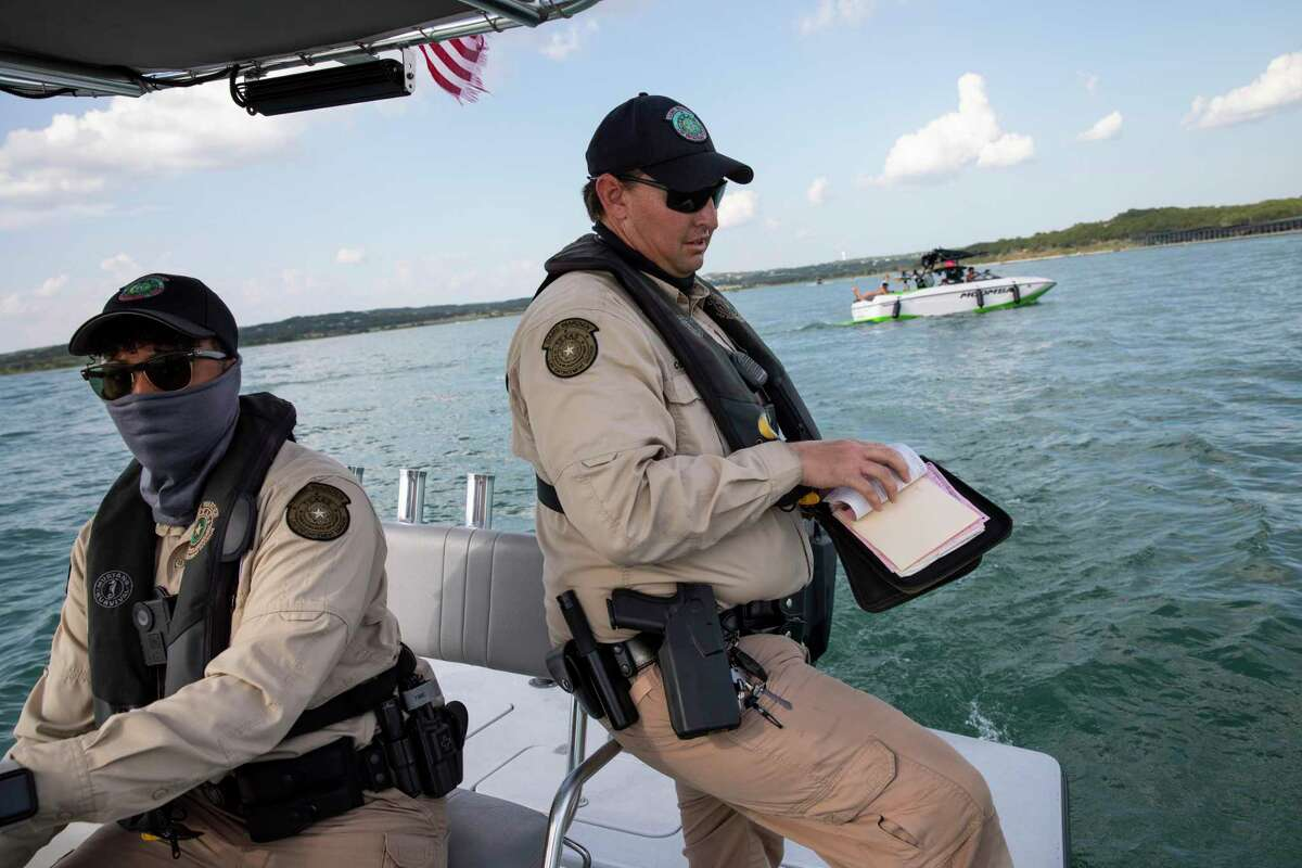 Texas Game Wardens Eric Cooper, 39, right, and Nicole Leonard, 33, left, finish writing a ticket to a boater for having an insufficient number of children?•s life jackets onboard to accommodate his children as the wardens enforce boating laws and safety on Canyon Lake in Spring Branch, Texas, U.S., on Sunday, September 6, 2020.