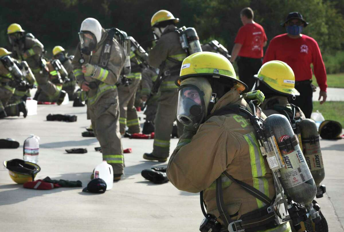 Student Jesse Segundo rushes to gear up during training at the academy, which is in Atascosa in Southwest Bexar County.