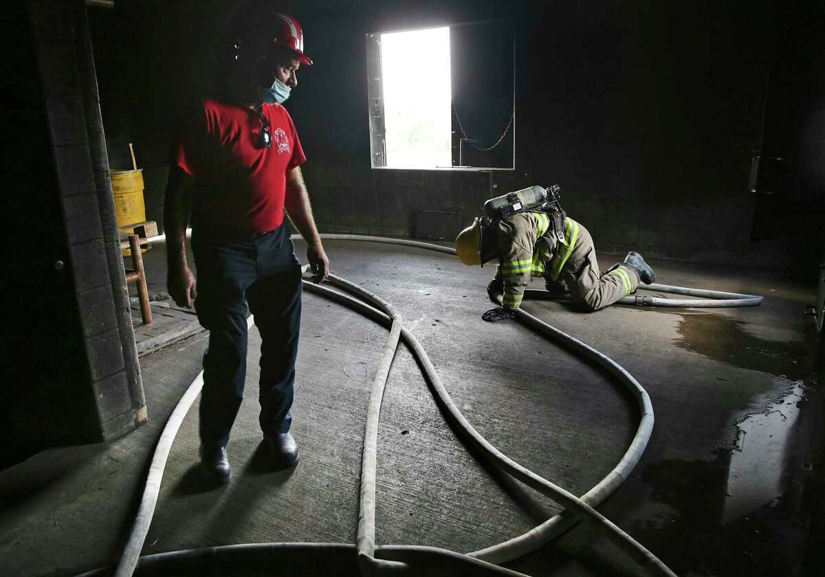 Instructor Capt. Bill Sanders, left, encourages a San Antonio College student at the First Responders Academy through a firefighter training course in which they must follow a hose out of a dark building to safety.