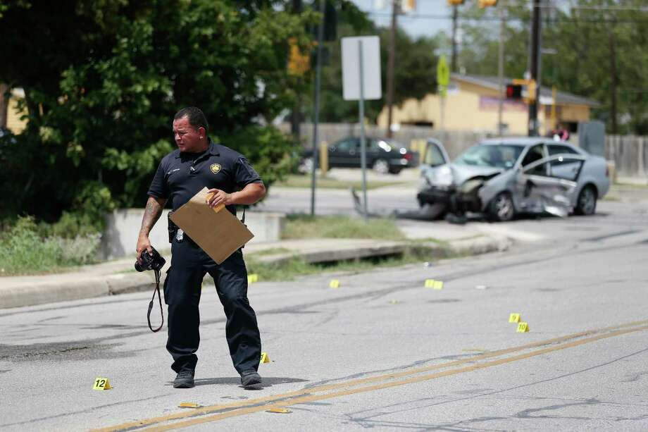 A San Antonio police evidence detective documents bullet casings Monday at the scene of a two-vehicle accident at the corner of Rigsby Avenue and Pecan Valley Drive. Evidence officers also tested several bags of a white powdery substance at the scene. About a mile away, officers were seen scraping paint off a white Chevrolet Tahoe. It is believed that the Tahoe and another vehicle were also involved with the accident scene. Photo: Photos By Jerry Lara / Staff Photographer / **MANDATORY CREDIT FOR PHOTOG AND SAN ANTONIO EXPRESS-NEWS/NO SALES/MAGS OUT/TV   © 2019 San Antonio Express-News