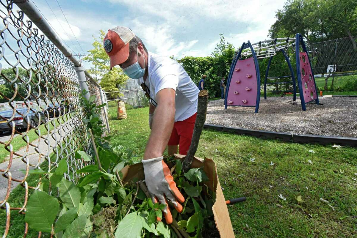Neil O'Connor of Albany prunes weeds around a fence during a Labor Day Pop Up Cleanup at Woodlawn Park on Monday, Sept. 7, 2020 in Albany, N.Y (Lori Van Buren/Times Union)