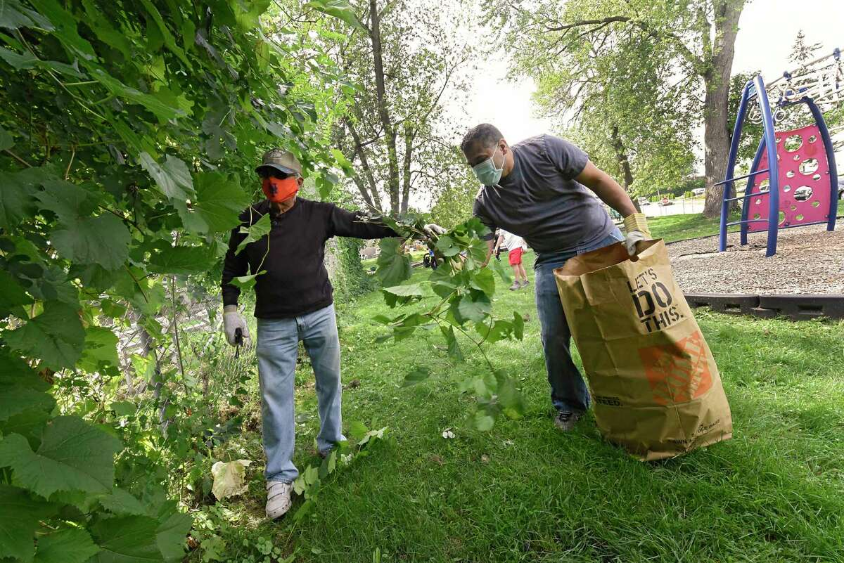 Volunteer Vic Consiglio, of Albany, left, hands Alfredo Balarin of Albany a handful of weeds he prunes around a fence during a Labor Day Pop Up Cleanup at Woodlawn Park on Monday, Sept. 7, 2020 in Albany, N.Y (Lori Van Buren/Times Union)